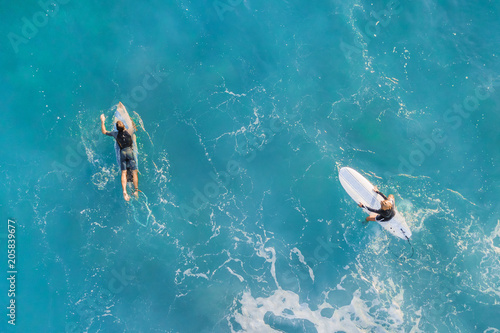 Two surfers in the ocean, top view