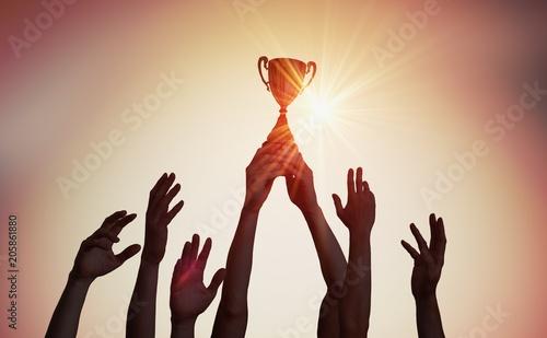 Obraz na plátně Winning team is holding trophy in hands