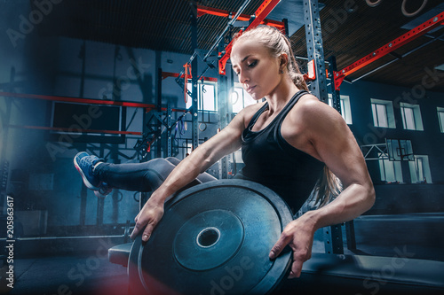 Obraz na plátně Fit young woman lifting barbells working out in a gym