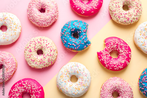 Delicious glazed doughnuts on color background, top view Fototapeta