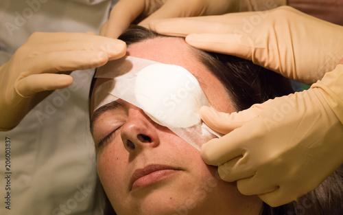 Fotografia, Obraz Doctor covering eye of patient by medical plaster