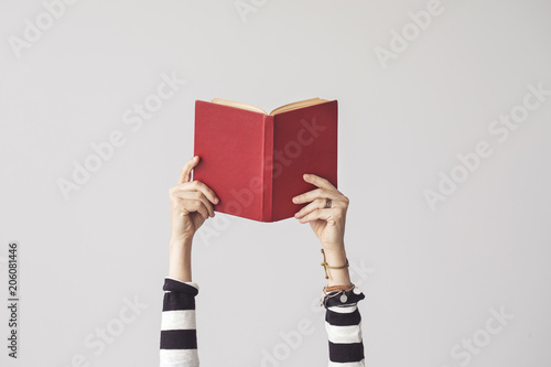 The hand holding book on isolated background