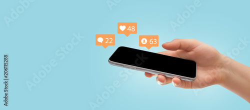 Female hand holding smartphone, surrounded with social media icons on blue background. Social media concept