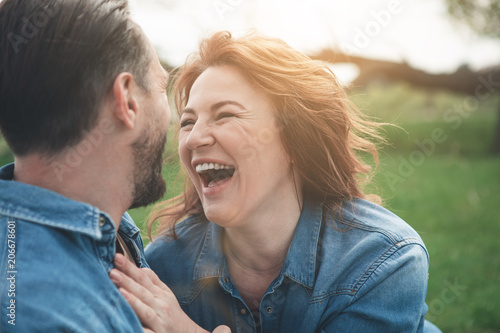 Carta da parati Portrait of excited middle-aged woman is laughing from the joke which man telling her