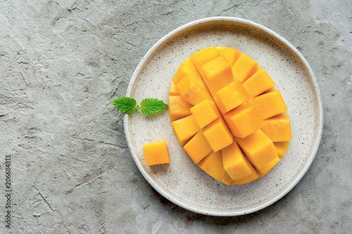 Healthy breakfast. Sliced mango fruit on plate. Top view. Concrete background. Minimal food photo.