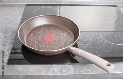 Frying pan on modern electric stove close up