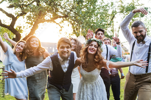 Tablou Canvas Bride, groom, guests posing for the photo at wedding reception outside in the backyard