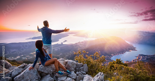 Happy couple watching the sunset in the mountains