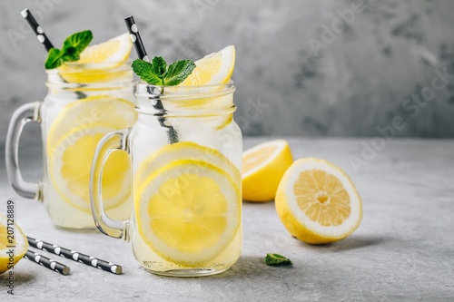 Homemade refreshing summer lemonade drink with lemon slices and ice in mason jars
