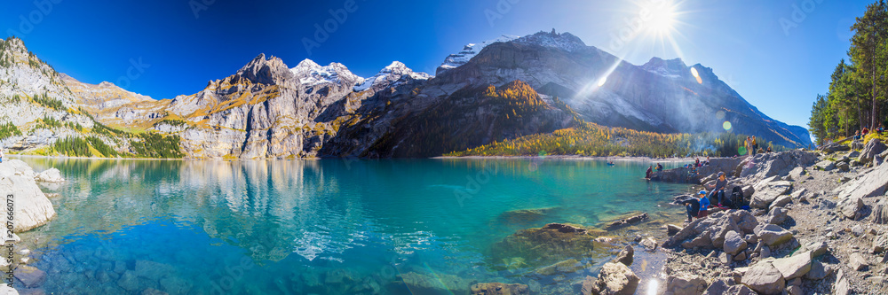 Amazing tourquise Oeschinnensee lake with waterfalls, wooden chalet and Swiss Alps, Berner Oberland, Switzerland