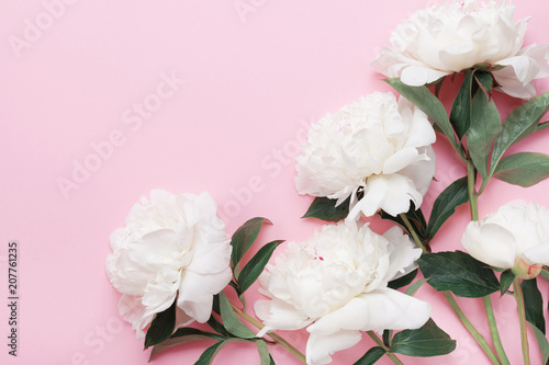 Beautiful white peony flowers bouquet on pink pastel table top view and flat lay style.