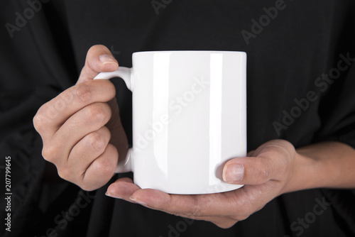 Hand Holding White coffee cup. mock up for creative design branding.