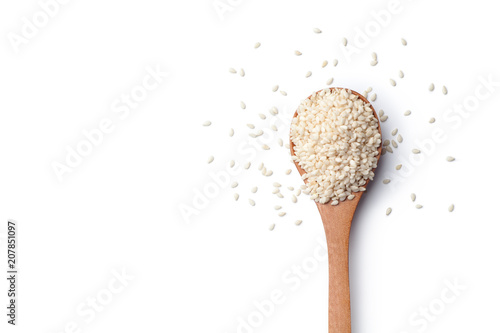 White sesame seeds in a wooden spoon on white background
