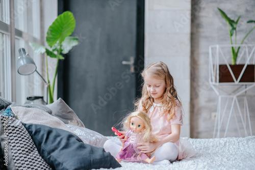 Happy child little girl kissing her favorite newborn doll Fototapeta