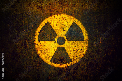 Fotografia Round yellow radioactive (ionizing radiation) danger symbol painted on a massive rusty metal wall with dark rustic grungy texture background with vignetting
