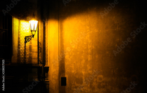 Old lantern illuminating a dark alleyway corner wall at night in Prague, Czech Republic. Photo almost monochromatic with brown yellow tones from the lantern as light source against the dark shadows