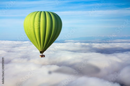 A lonely green hot air balloon floats above the clouds. Concept leader, success, loneliness, victory