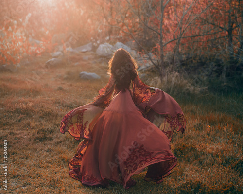 Canvas Print A brunette girl with wavy, thick hair runs to the meeting of the sun