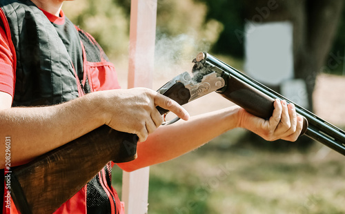 Photo man opens the shotgun bolt after one shot with smoke