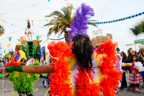 Unidentified blurry carnival dancer on street parade outdoors background. Back view unrecognizable silhouette of joyful dance performers