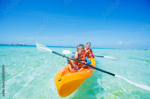 Canvas Print Happy boy and girl kayaking at tropical sea on yellow kayak