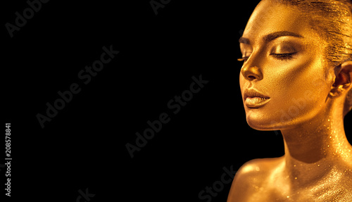 Golden skin woman face. Fashion art portrait closeup. Model girl with holiday golden glamour shiny professional makeup. Gold jewelry, accessories