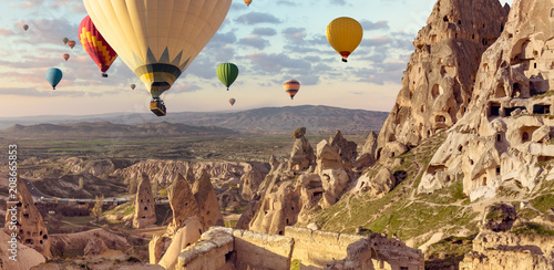 Air balloons above Turkish National Park in Goreme. Panorama of Cappadocia landscape - multi colored balloons flying over mountain valley of ancient cave town Uchisar.