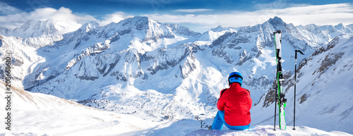 Canvas Print Young happy skier sitting on the top of mountains and enjoying view of Rhaetian