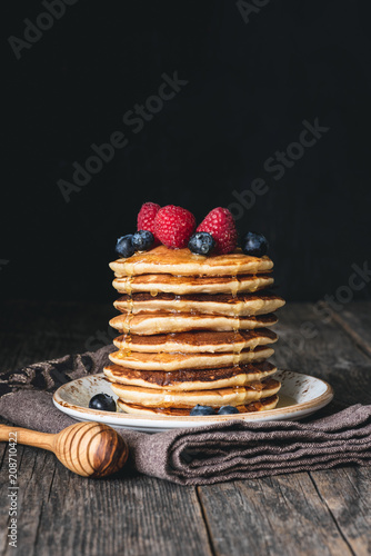 Stack of pancakes with honey and fresh berries on wooden table over dark background. Selective focus, copy space for text