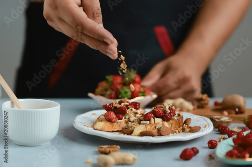 Sweet sandwiches with little strawberries, cheese, camembert, brie, nuts and honey on the whole grain bread bruschetta cooking by chef hand on light background