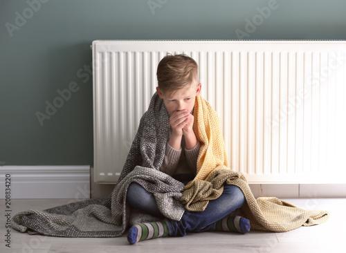 Fotografia Sad little boy suffering from cold on floor near radiator
