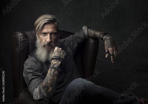 Fototapeta Portret wytatuowany brodaty mężczyzna siedzi na fotelu