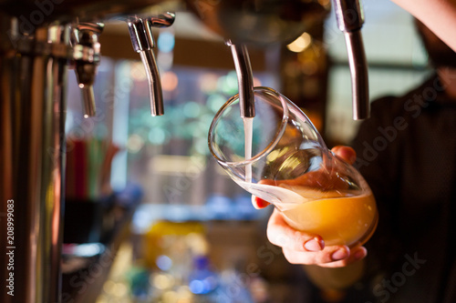 The barman pours light unfiltered beer from the tap фототапет