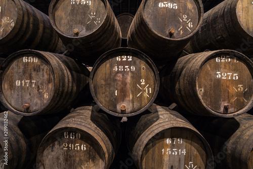 Stampa su Tela Row of wooden porto wine barrels in wine cellar Porto, Portugal.
