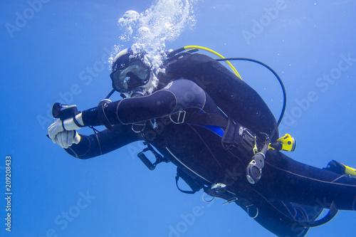 Taucher mit Ausrüstung Unterwasser im Meer taucht am Betrachter seitlich vorbei