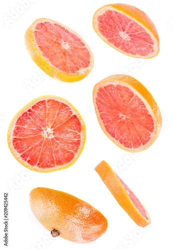 sliced flying grapefruit isolated on white background with clipping path. cut grapefruit in pieces isolated on white background. Levity fruit floating in the air