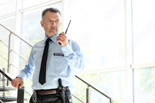 Fotografie, Obraz Male security guard using portable radio transmitter indoors