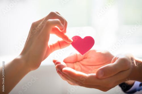 Woman Giving Heart On Man's Hand Fototapet