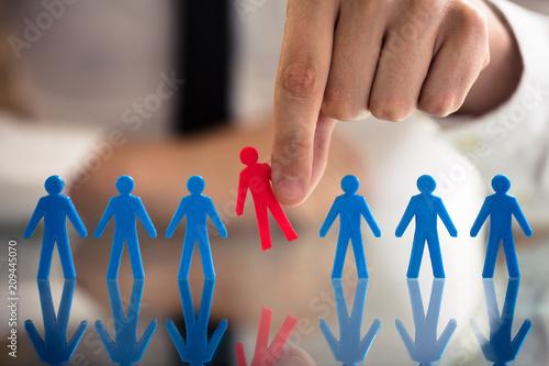 Obraz na plátně Businessperson Picking Red Human Figures