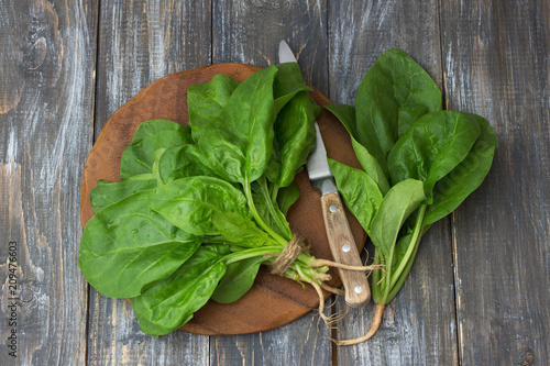 Bunch of fresh spinach with roots on a cutting board with a knife. on a wooden table. rustic style
