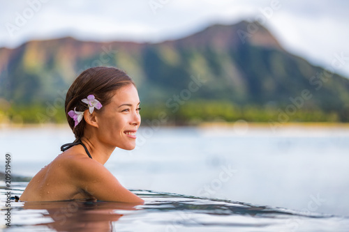 Asian woman relaxing in infinity pool at luxury spa resort in Hawaii, watching ocean beach from hotel. Girl tourist on travel vacation in Waikiki, Honolulu, USA holiday. Summer outdoor wellness.