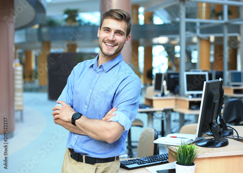 Foto Young man posing confident and positive in professional workplace office with space