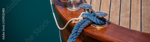 Photo dock cleat on the side of a boat in a small marina, an element of yachting equip