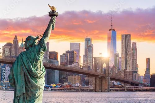 Photo Statue Liberty and  New York city skyline at sunset