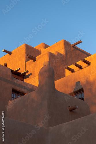 Fototapeta premium Budynek w stylu Adobe pueblo świecący o zachodzie słońca w Santa Fe w Nowym Meksyku