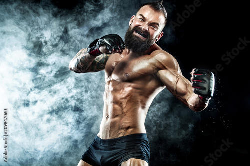 Canvas Print Sportsman boxer fighting on black background with smoke