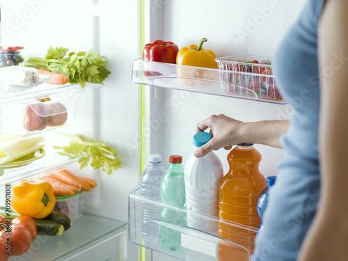 Woman taking a bottle of milk from the fridge