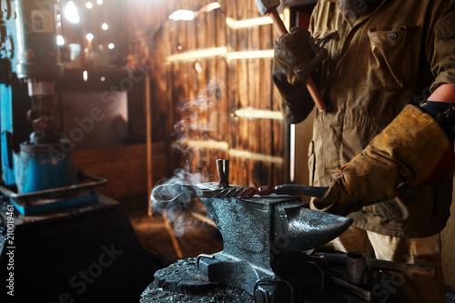 Fotografia The blacksmith forging the molten metal on the anvil in smithy.