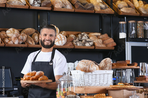 Tableau sur Toile Male baker holding wooden board with delicious croissants in shop