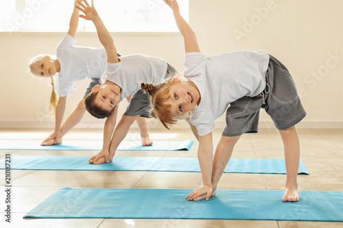 Little children practicing yoga indoors
